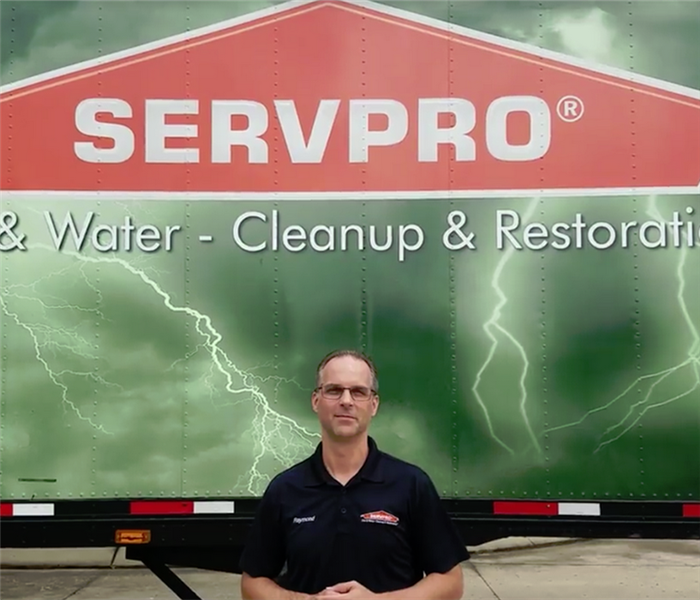 Male SERVPRO owner in front of the logo