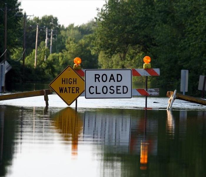 Flooded street. High water and road closed sign