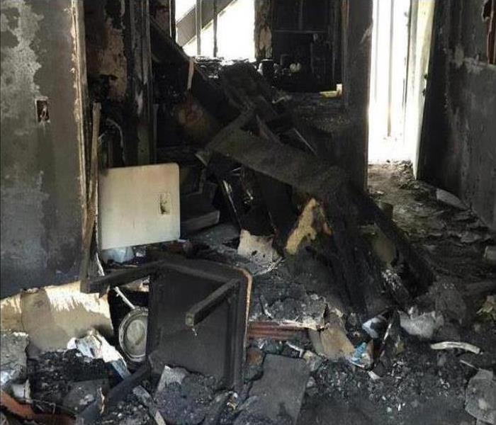 A room covered in debris, soot and smoke damage after a fire