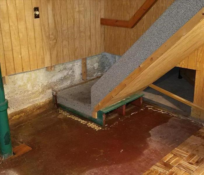 A basement floor with standing water.